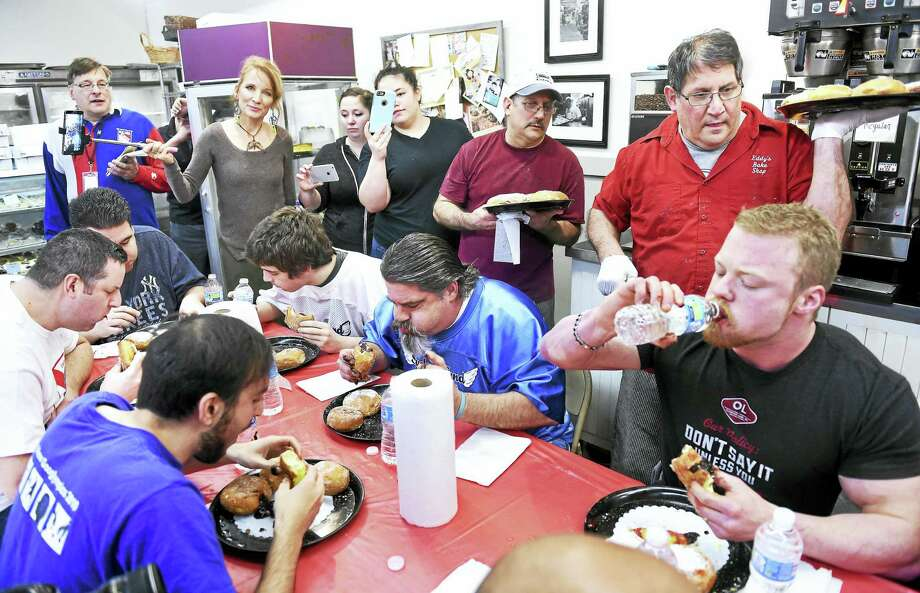 Paul Ciocca, top right, owner of Eddy's Bake Shop, watches Nick Wehry, bottom right, of Torrington on his way to winning the 19th annual paczki eating contest in Ansonia Tuesday. Photo: Arnold Gold — New Haven Register