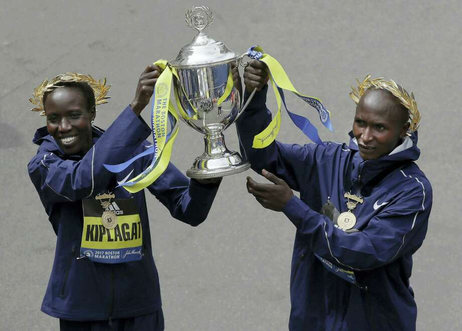Kenyan's Edna Kiplagat, left, and Geoffrey Kirui hold a trophy together after their victories in the 121st Boston Marathon on Monday. Photo: Charles Krupa — The Associated Press  / Copyright 2017 The Associated Press. All rights reserved.