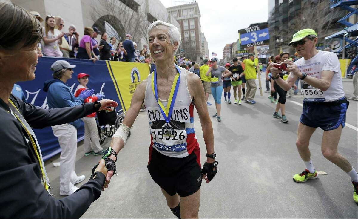 Multi-time Boston Marathon winner Uta Pipping, left, congratulates Ben Beach, brother of New Haven Register columnist, after he finished running his 50th consecutive Boston Marathon on Monday.