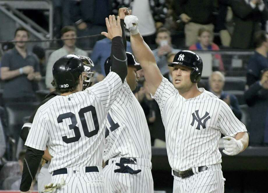 Yankees left fielder Matt Holliday, right, celebrates with Aaron Hicks and Pete Kozma (30) after Holliday hit a three-run home Monday. Photo: Bill Kostroun — The Associated Press  / FR51951 AP