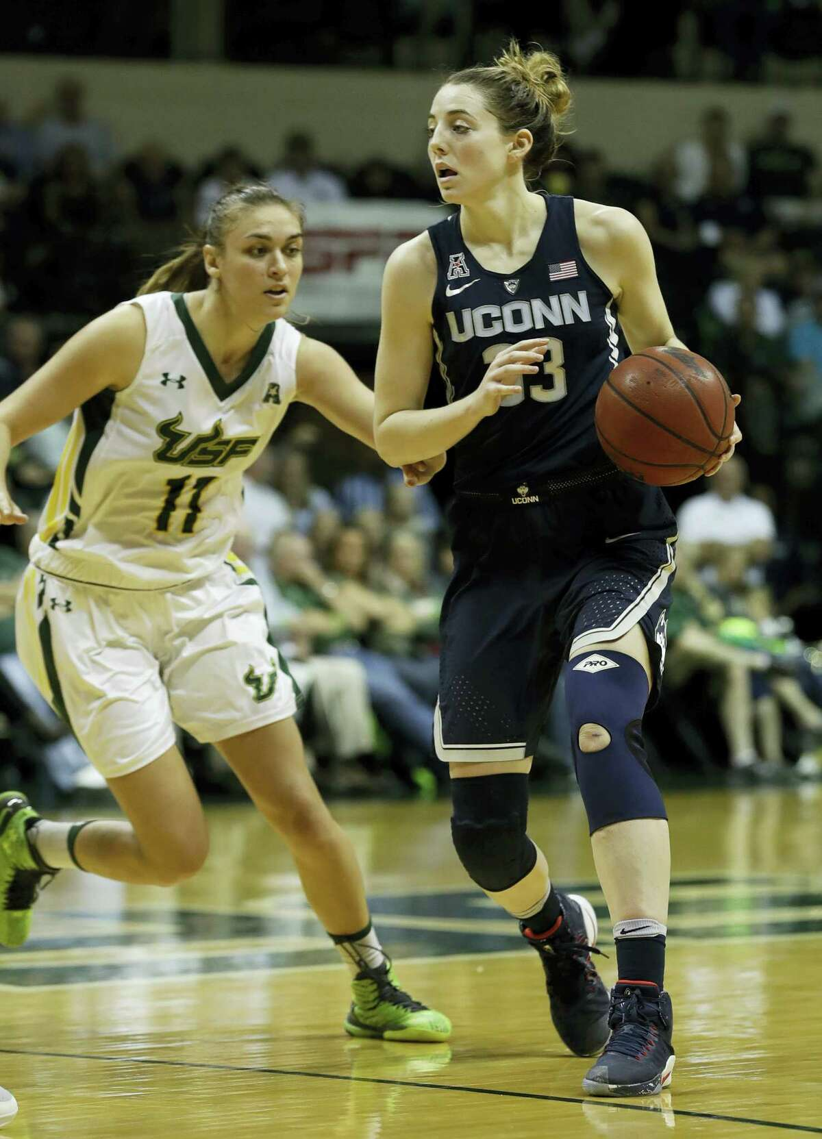 Connecticut guard/forward Katie Lou Samuelson (33) drives around South Florida guard/forward Ariadna Pujol (11) during the second half of an NCAA women's college basketball game Monday in Tampa, Fla. UConn won the game 96-68.