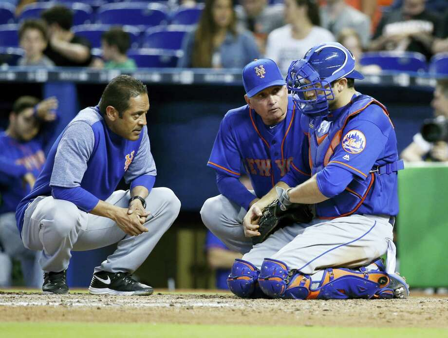New York Mets manager Terry Collins, center, and a trainer attend to catcher Travis d'Arnaud after a play during the ninth inning Sunday. Photo: Wilfredo Lee — The Associated Press  / Copyright 2017 The Associated Press. All rights reserved.