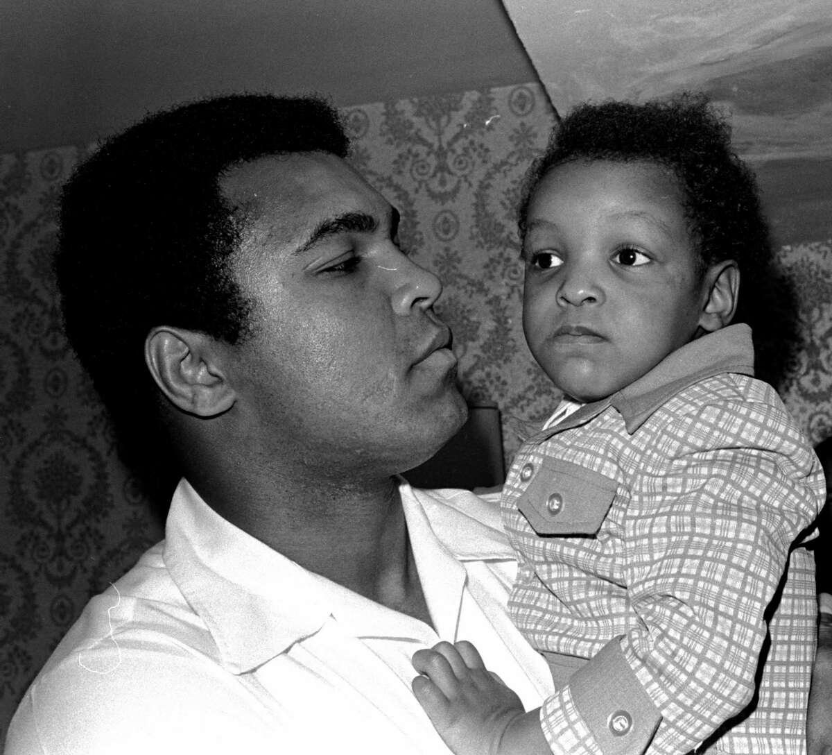 In this April 15, 1975 photo, Heavyweight boxing champion Muhammad Ali, and Little Muhammad Ali, his 2 1/2 year old son, arrive at Miami Beach, Fla. Muhammad Ali's son, who bears the boxing great's name, was detained by immigration officials at a Florida airport and questioned about his ancestry and religion in what amounted to unconstitutional profiling, a family friend said on Feb. 25, 2017.