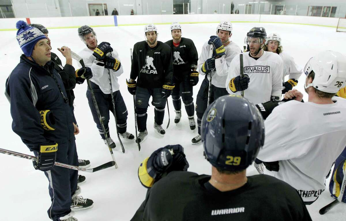 Former Buffalo Sabres player Andrew Peters, left, and Sabres players talk during a workout.