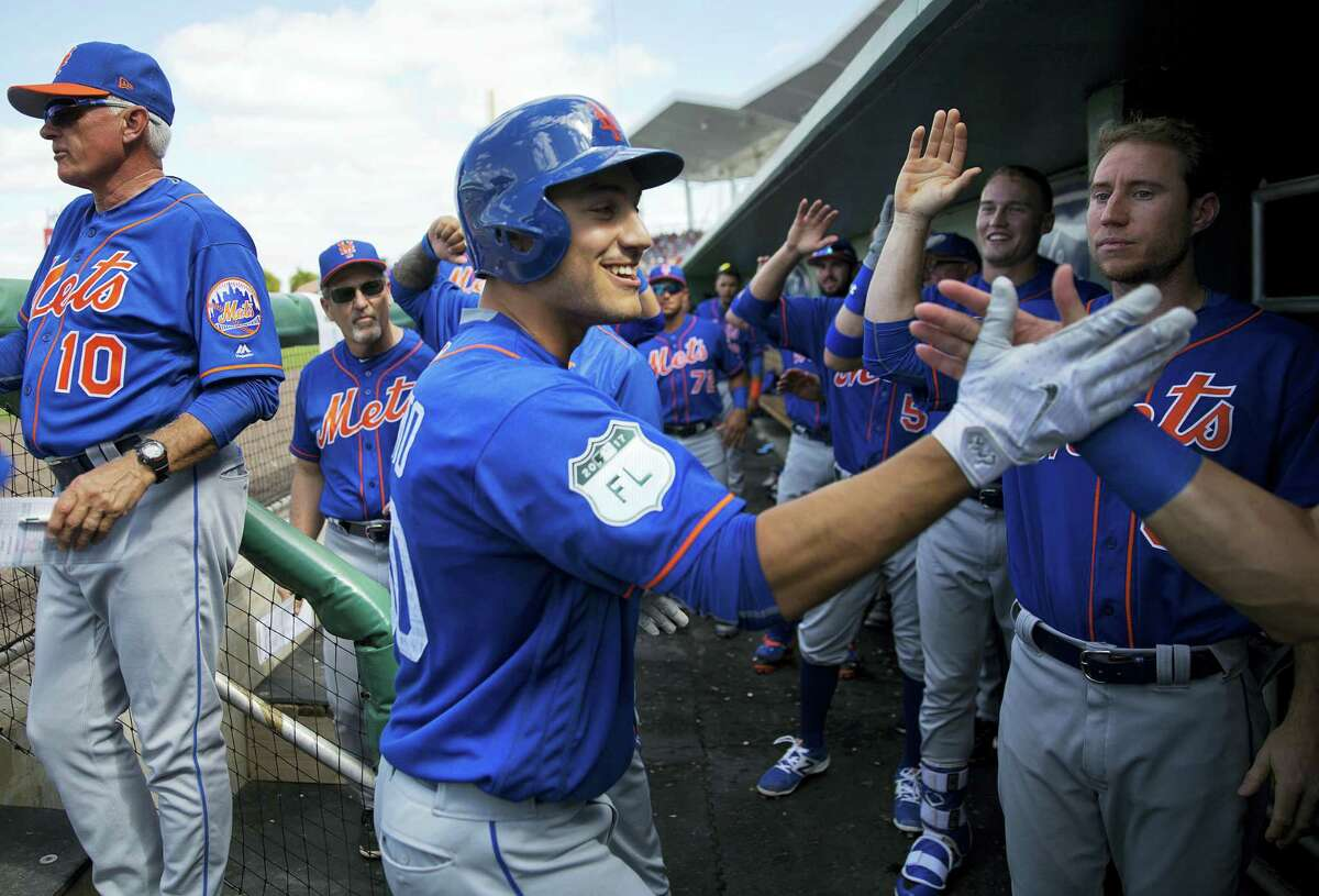 New York Mets' Michael Conforto, center, high-fives teammates after hitting a home run in the third inning of an exhibition game against the Red Sox on Friday.