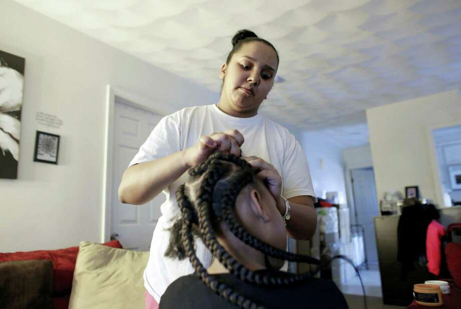 In this Feb. 19, 2017 photo Jocelyn DoCouto, top, adds braid extensions for seven-year-old Zanyrah Parrott, of Pawtucket, R.I., in DoCouto's home, in Pawtucket. The billionaire industrialist Charles Koch might not have a lot in common with DoCouto, but they are both part of a national movement to deregulate the business of African-style braiding. DoCouto is pushing for state legislation in Rhode Island that would exempt her from the cumbersome and expensive occupational licensing requirements for hairdressers and barbers. Photo: AP Photo/Steven Senne  / Copyright 2017 The Associated Press. All rights reserved.