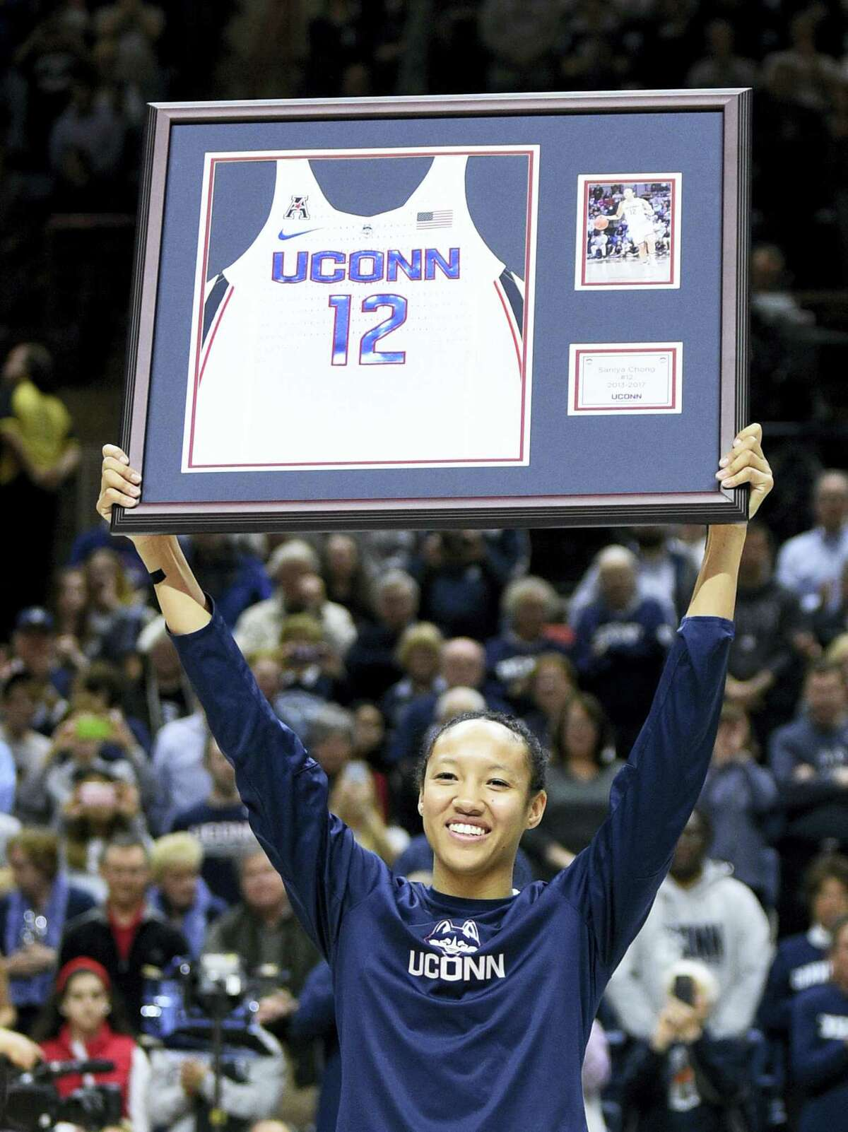 UConn's Saniya Chong holds aloft a plague on senior day before Saturday's game against Memphis in Storrs.
