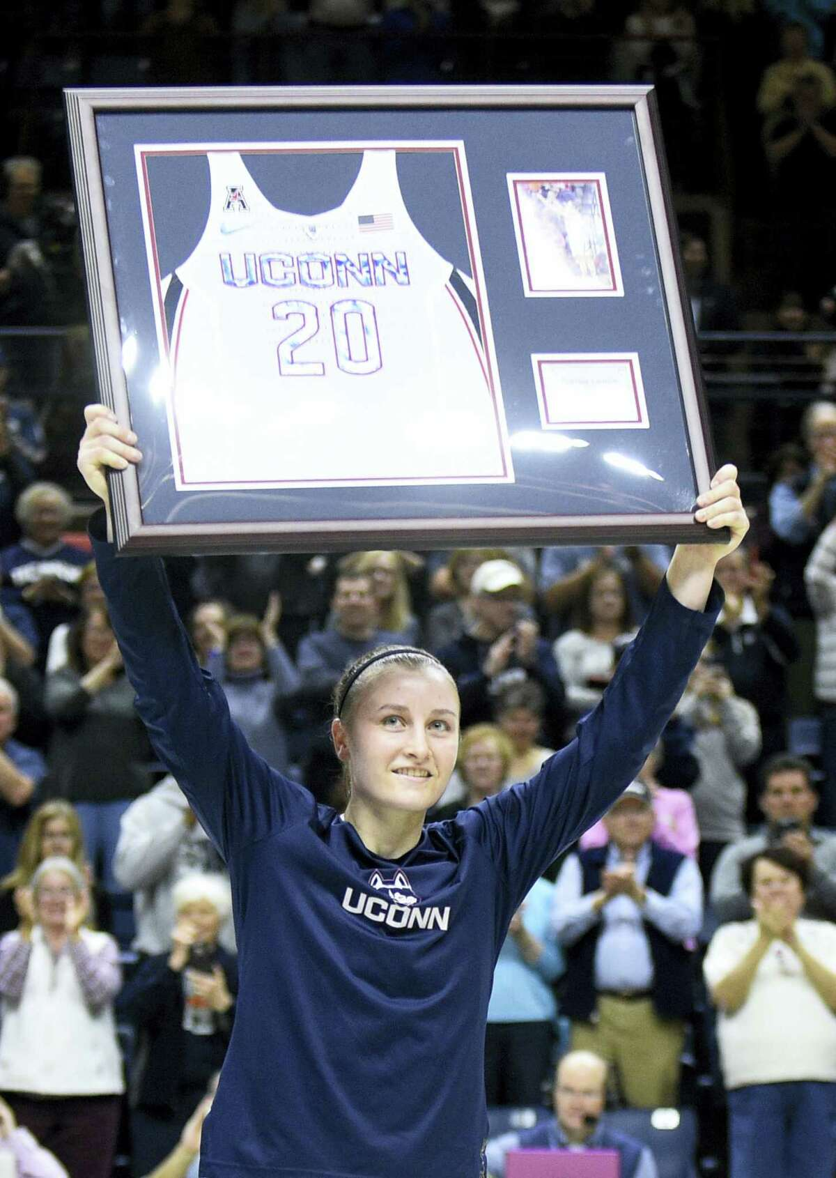UConn's Tierney Lawlor holds aloft a plague with her jersey number on Saturday.