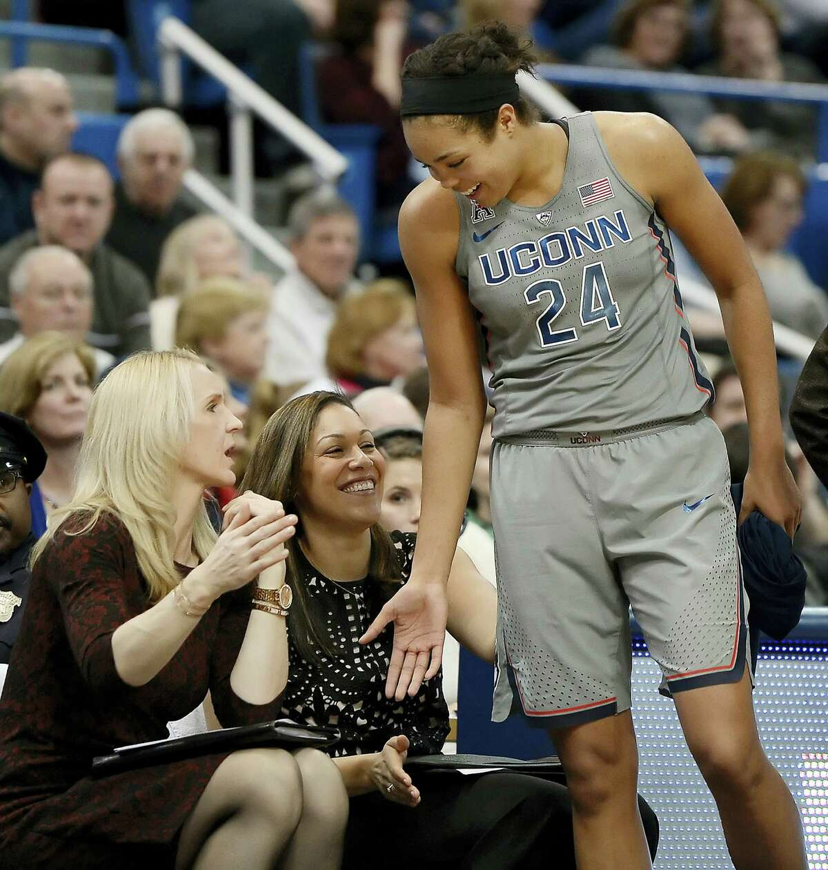 UConn assistant coaches Shea Ralph, left, and Marisa Moseley, center, congratulate Napheesa Collier as she comes out of the Huskies game against Temple.