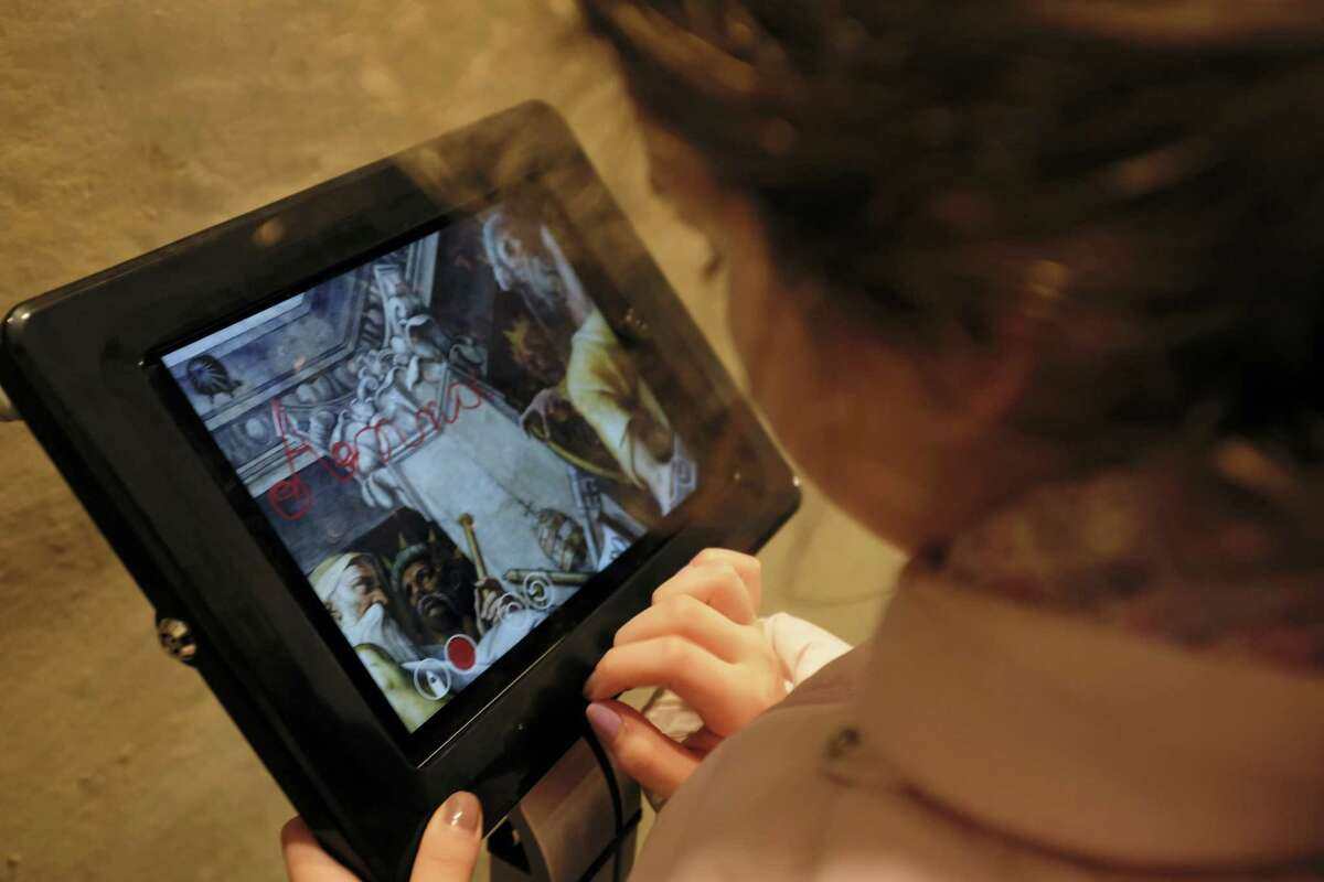 A woman looks at a touch screen placed inside the dome of Santa Maria del Fiore Cathedral where visitors can leave a digital message, in Florence, Italy, in this Feb. 21, 2017 photo made available on Thursday, Feb. 23, 2017. Florence's famed Duomo is cleaning up its act, removing centuries of graffiti from the cathedral dome interior and letting new visitors leave their mark digitally instead.