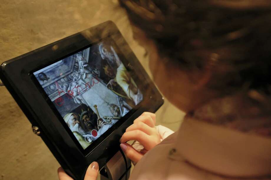 A woman looks at a touch screen placed inside the dome of Santa Maria del Fiore Cathedral where visitors can leave a digital message, in Florence, Italy, in this Feb. 21, 2017 photo made available on Thursday, Feb. 23, 2017. Florence's famed Duomo is cleaning up its act, removing centuries of graffiti from the cathedral dome interior and letting new visitors leave their mark digitally instead. Photo: Claudio Giovannini/Opera Di Santa Maria Del Fiore Via AP   / Opera di Santa Maria del Fiore