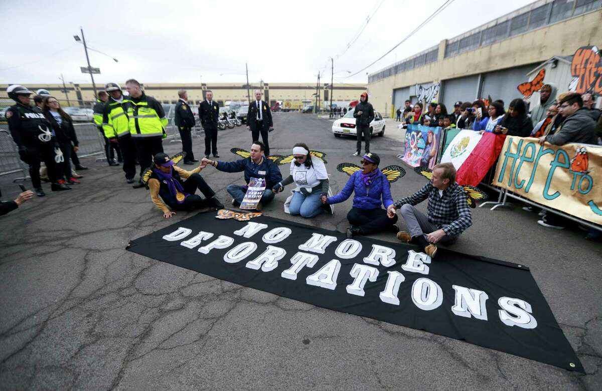 Activists block a street as police officers look on during an immigration protest outside of a detention center, Thursday, Feb. 23, 2017, in Elizabeth, N.J. The activists were taken into custody after they refused to clear the street.