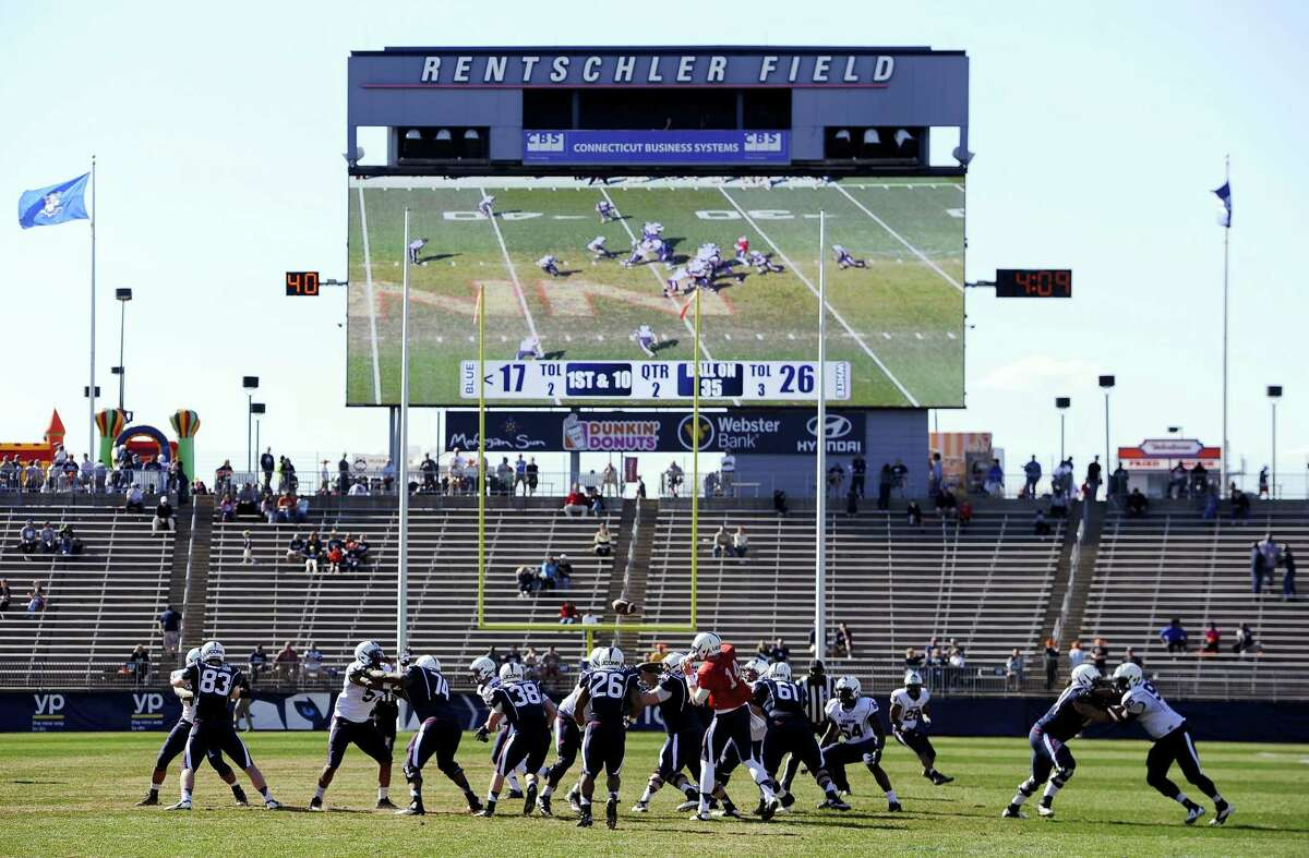 """In this April 12, 2014 photo, Connecticut players run a play during the first half of UConn's Blue-White spring NCAA college football game at Rentschler Field, in East Hartford, Conn. UConn is moving forward with plans to build new athletic facilities for its soccer, baseball and softball teams. The school's board of trustees is expected to vote Wednesday, Feb. 22, 2017, to spend the first $4.75 million dollars to design the school's """"Athletic District,"""" where the fields will be located."""