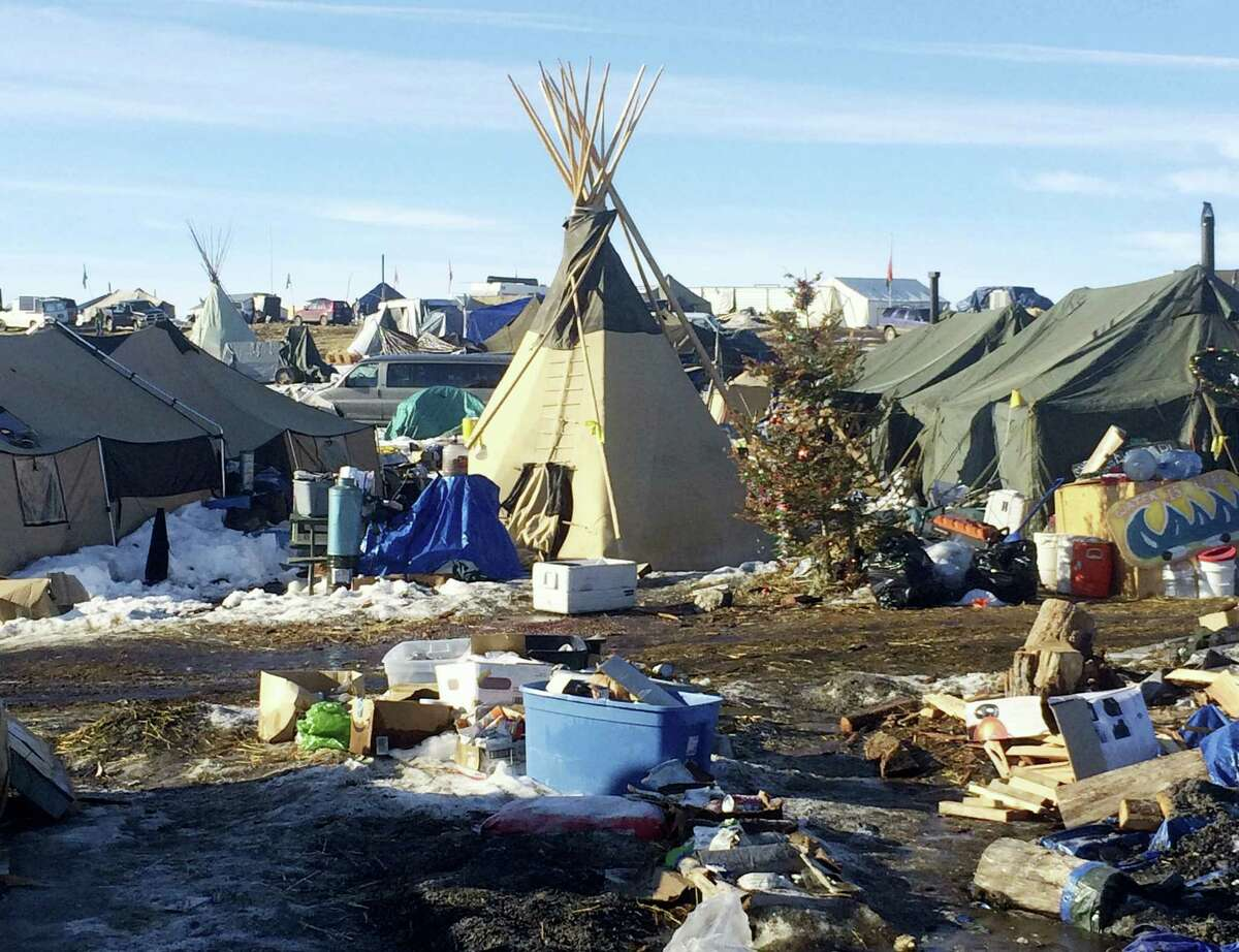 In this Feb. 16, 2017 photo, debris is piled on the ground awaiting pickup by cleanup crews at the Dakota Access oil pipeline protest camp in southern North Dakota near Cannon Ball. The camp is on federal land, and authorities have told occupants to leave by Wednesday, Feb. 22 in advance of spring flooding.