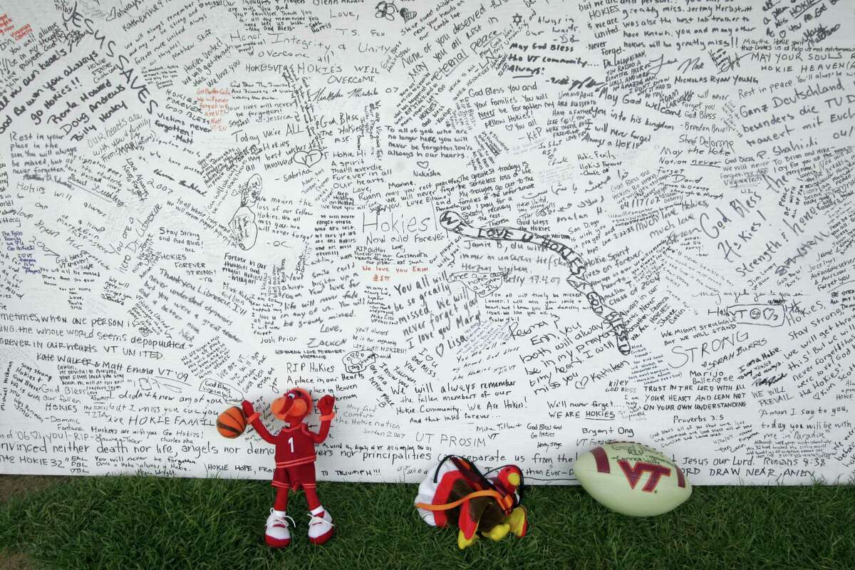 FILE - In this April 28, 2007 file photo, a memorial board sits under a tent with items that were placed in front of it, on the Drillfield on the Virginia Tech campus in Blacksburg, Va. Ten years after a mentally ill student fatally shot 32 people at Virginia Tech, survivors and families of the slain are returning to campus to honor the lives that were lost that day. Virginia Tech is holding a series of events Sunday, April 16, 2017 to mark the anniversary of the deadly campus shooting on April 16, 2007. (AP Photo/Alex Brandon, File)