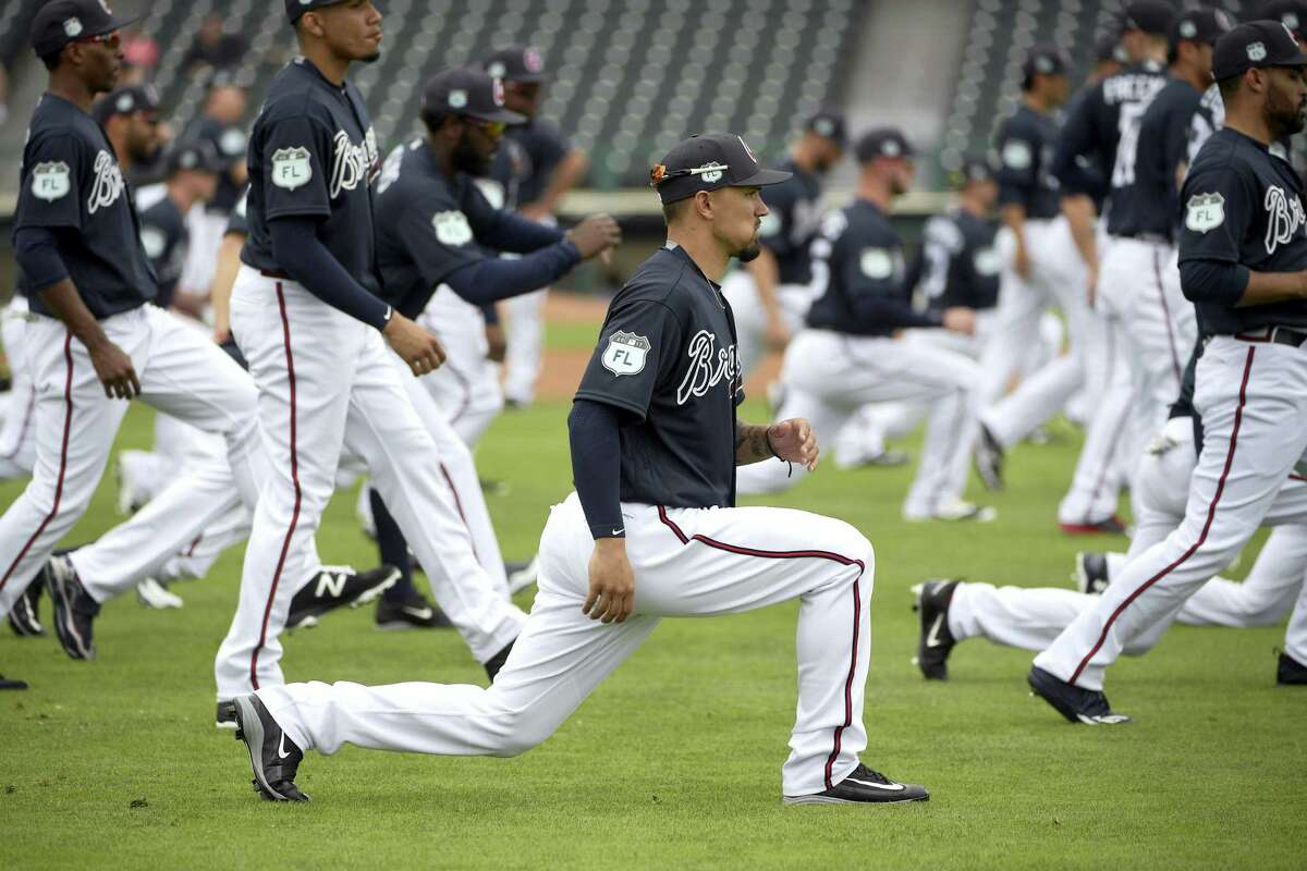 Atlanta Braves infielder Jace Peterson, center, stretches with teammates during the first full-squad spring training workout in Lake Buena Vista, Fla. on Feb. 18, 2017.