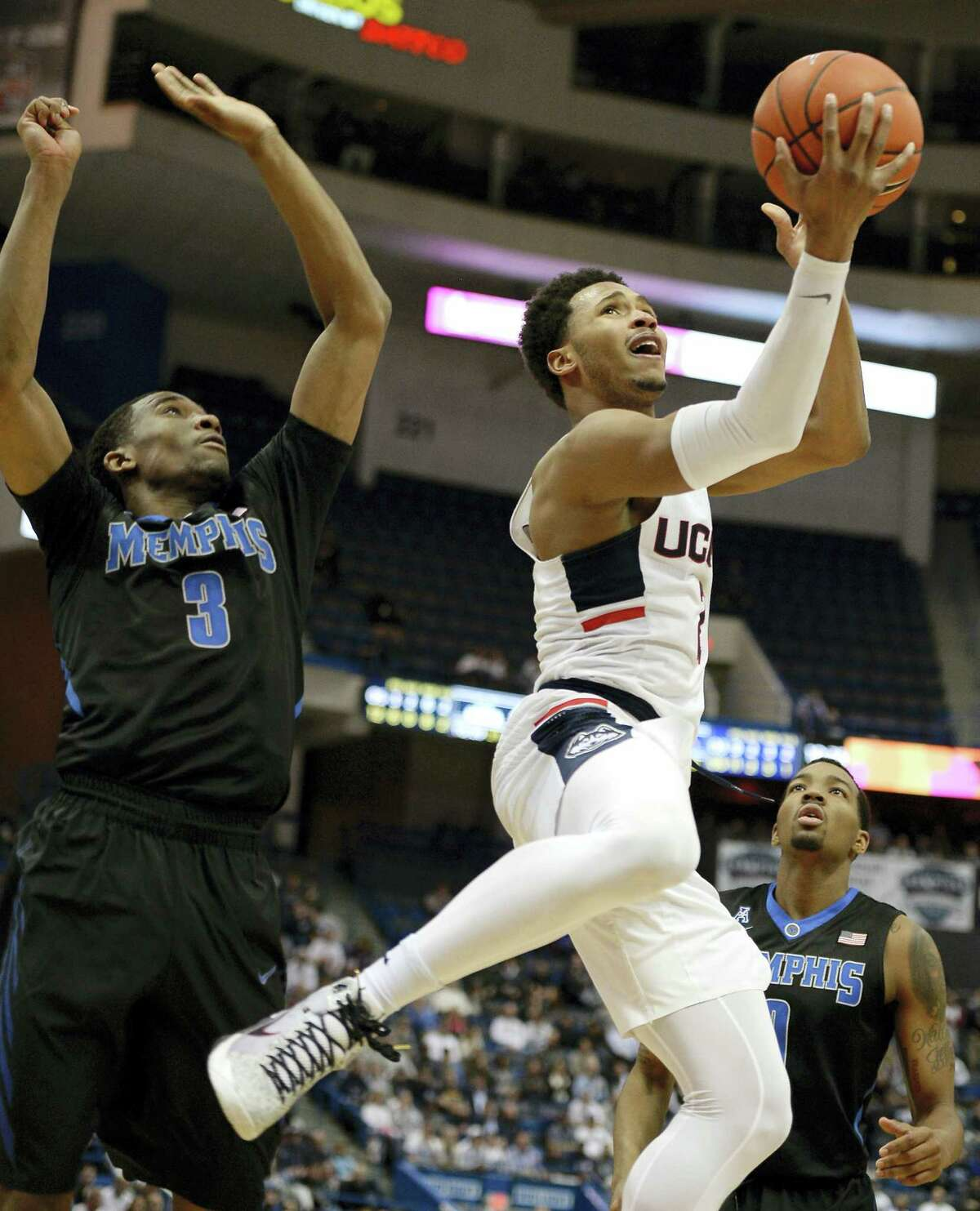 JESSICA HILL — THE ASSOCIATED PRESS UConn's Jalen Adams, right, shoots a basket as Memphis' Jeremiah Martin, left, defends in the second half of the Huskies' win last Thursday. UConn plays at Houston Wednesday night.