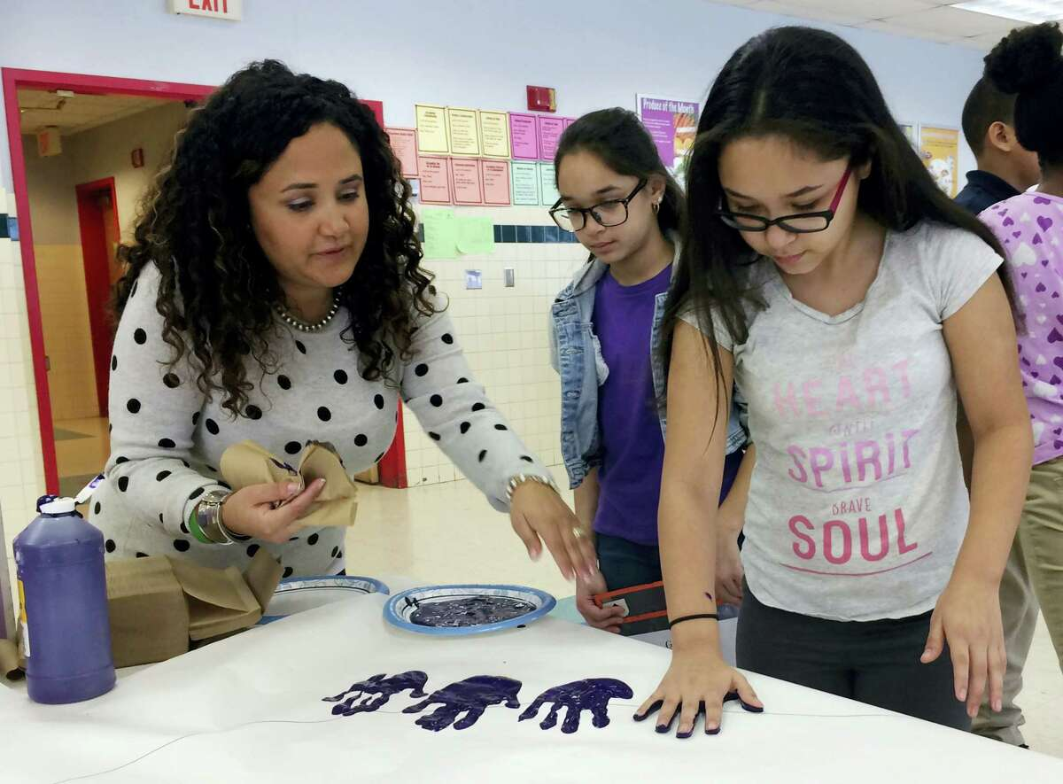 In this Feb. 14, 2017 photo, Nelba Marquez-Greene helps 10-year-old Araceli Buchko put her hand print inside a giant paper heart as part of the Love Win's campaign's Friendship Day, a social and emotional learning activity at the Chamberlain Elementary School in New Britain, Conn.