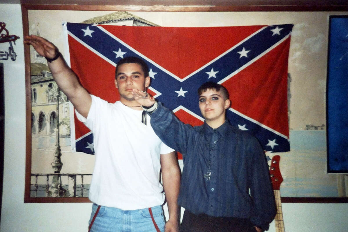 This undated photo provided by Christian Picciolini shows him at left with Shannon Martinez giving Nazi salutes while both were affiliated with racist skinhead organizations as young people decades ago. Picciolini went on to begin Life After Hate, a nonprofit that works to get people out of extremist groups, and Martinez volunteers by talking to people in an online forum sponsored by the organization.
