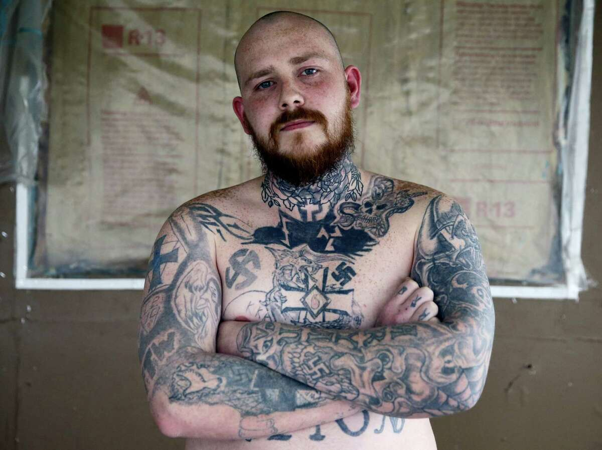 In this Thursday, Jan. 12, 2017 photo, Shane Johnson displays some of his tattoos as he poses in his home in Tippecanoe, Ind. Johnson was born into extremism is in the process of covering some of his racist tattoos with new ones and wears long sleeves to hide remnants of his past he regrets. His father and many of his father's relatives were part of the Klan, he said, so there was only one real way for him to go as a youth. (AP Photo/Michael Conroy)