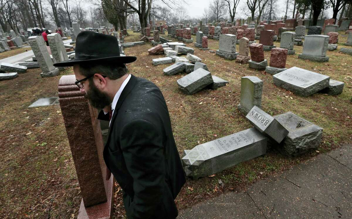 """Rabbi Hershey Novack of the Chabad center walks through Chesed Shel Emeth Cemetery in University City, Mo., on Tuesday, Feb. 21, 2017, where almost 200 gravestones were vandalized over the weekend. """"People who are Jewish are shocked and angry,"""" Novack said."""