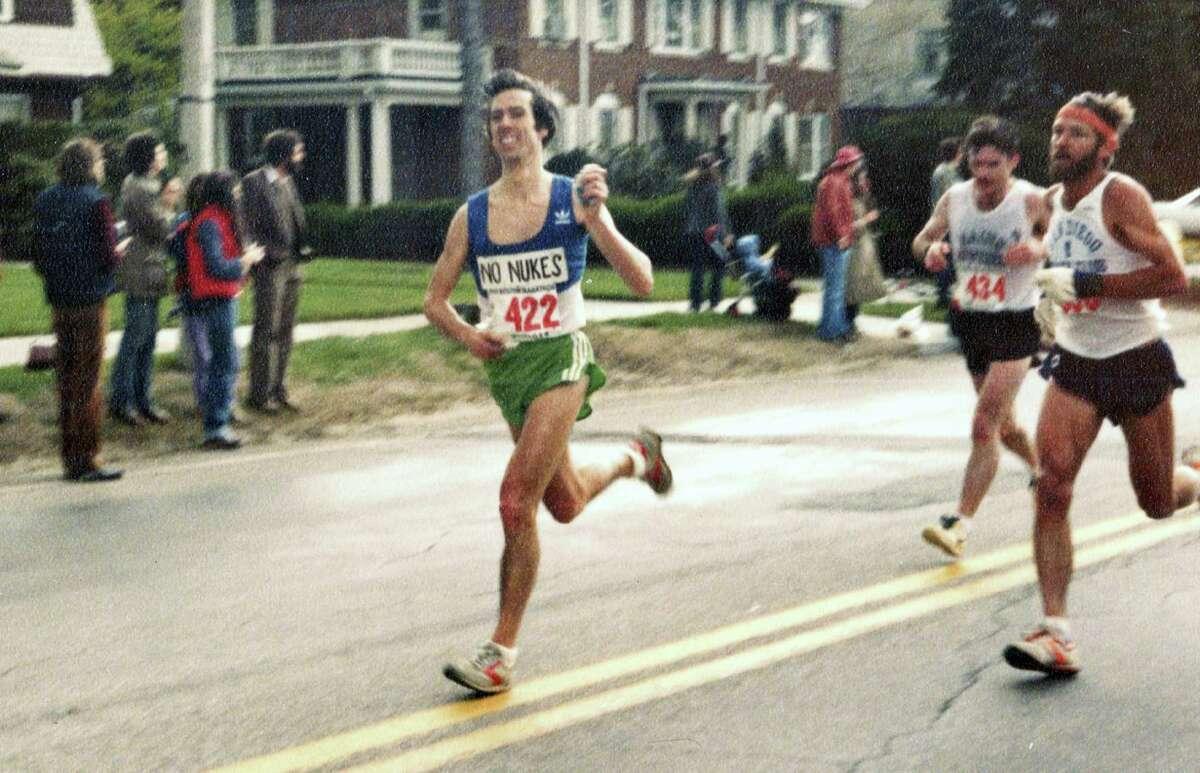 In this photo provided by Carol M. Beach, her husband Ben Beach, age 31, runs along the Boston Marathon course in Newton, Mass.