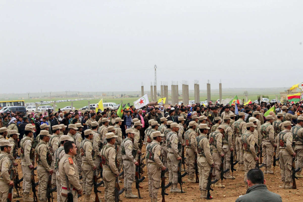 This photo provided by Hawar News Agency, a Kurdish-run news agency, which has been authenticated based on its contents and other AP reporting, shows fighters from the predominantly-Kurdish Syrian Democratic Forces attending the funeral procession of 18 of their comrades, who were killed Tuesday by a misdirected airstrike by the U.S.-led coalition, in Tal al-Abyad, northeast Syria, Thursday, April 13, 2017. U.S. Central Command said coalition aircraft were given the wrong coordinates by their partner forces, the Syrian Democratic Forces, for a strike intended to target Islamic State militants south of their Tabqa stronghold. (Hawar News Agency via AP)