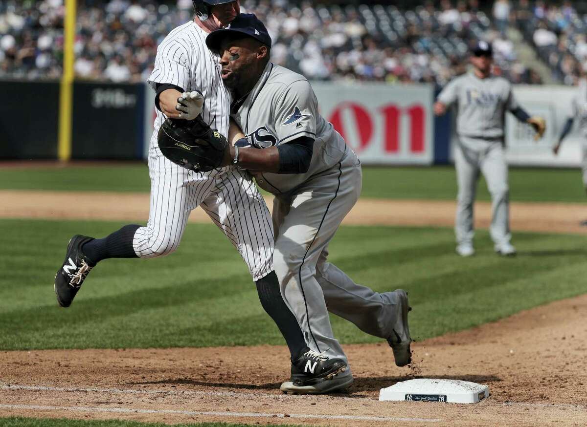 New York Yankees' Brett Gardner, left, collides with Tampa Bay Rays first baseman Rickie Weeks as Weeks reaches for an errant throw by pitcher Xavier Cedeno during the sixth inning of a baseball game, Wednesday, April 12, 2017, in New York. Chase Headley scored on the play. Both Weeks and Gardner left the game. (AP Photo/Julie Jacobson)