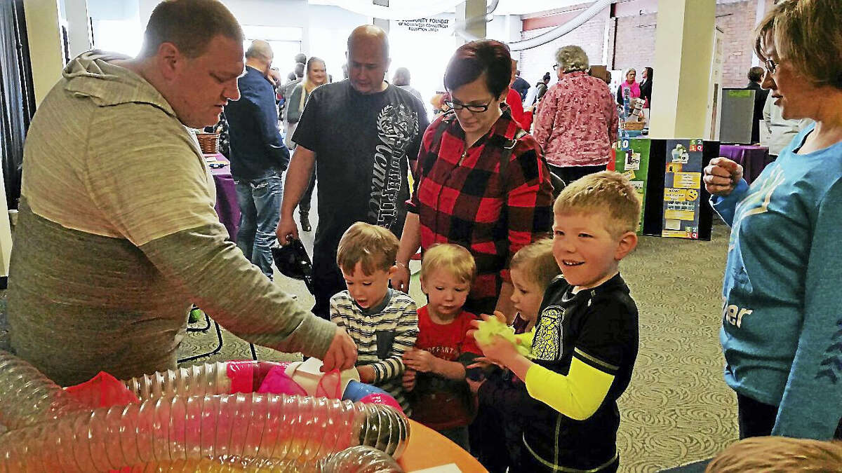 Children put colorful scarves into a 100-foot transparent pneumatic tube to learn about physics at the KidsPlay Children's Museum's third annual Family Fun Fair.