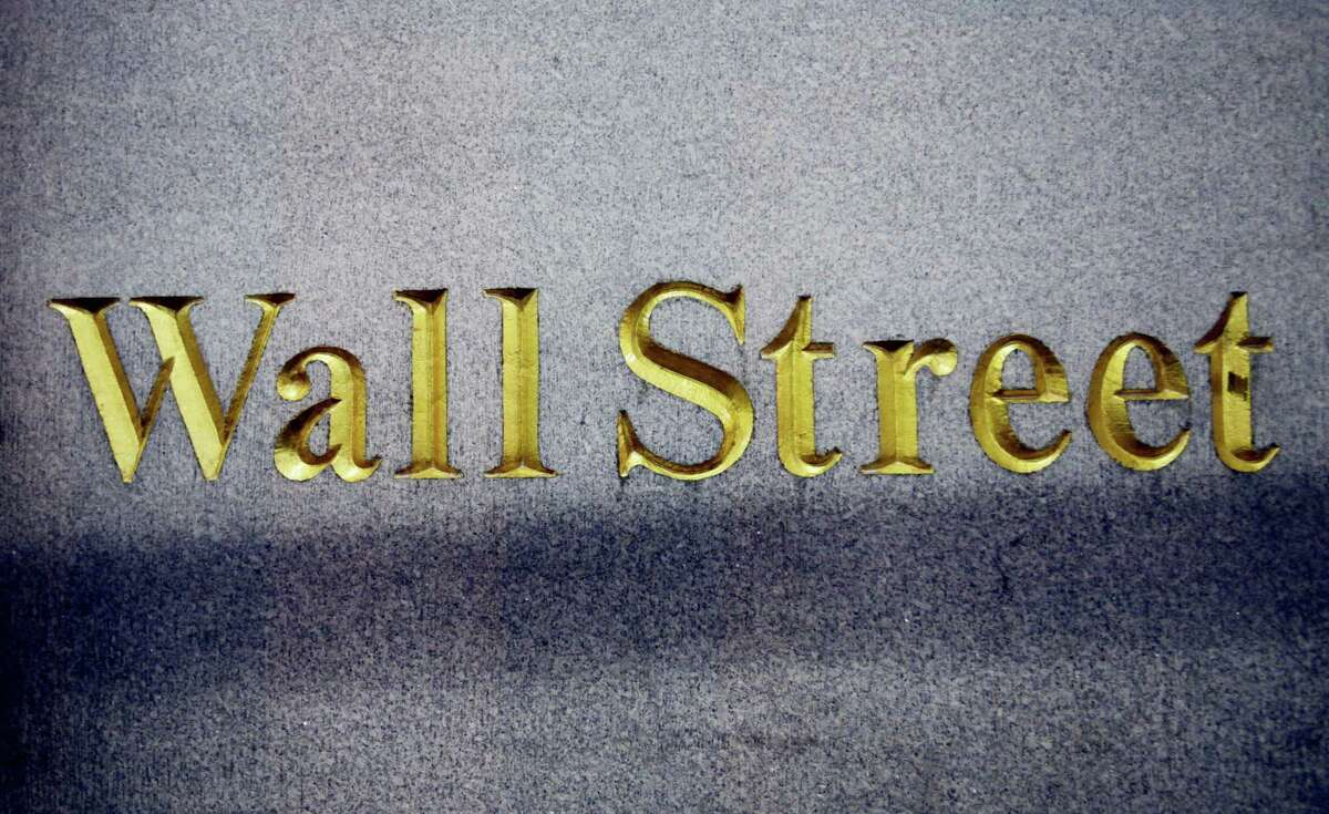 FILE - In this Oct. 8, 2014, file photo, a Wall Street address is carved in the side of a building in New York. U.S. stock indexes edged lower in early trading Wednesday, April 12, 2017, weighed down mainly by a slide in materials and industrial companies. Consumer goods stocks were up the most. Energy stocks also rose as crude oil prices headed higher. Trading was subdued as investors monitored brewing geopolitical tensions head of the long Easter holiday weekend.