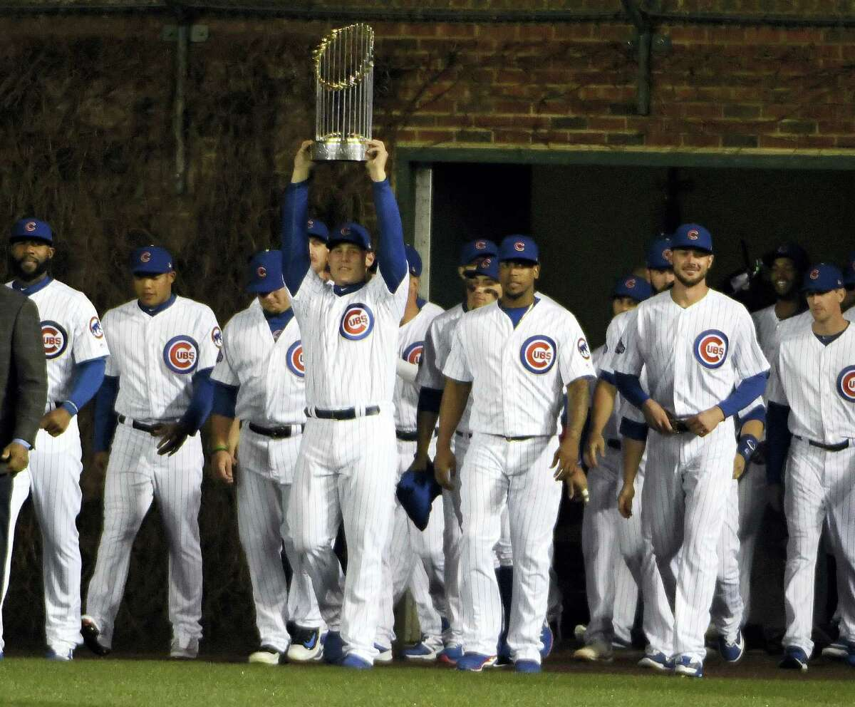 Chicago Cubs first baseman Anthony Rizzo (44) carries the 2016 World Series Championship trophy before a baseball game between the Chicago Cubs and the Los Angeles Dodgers on home opening day April 10, 2017 in Chicago.