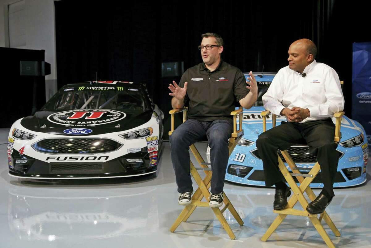 Team owner Tony Stewart, left, answers a question as Raj Nair, Executive VP for Global Product Development and Chief Technical Officer, Ford Motor Company, listens.