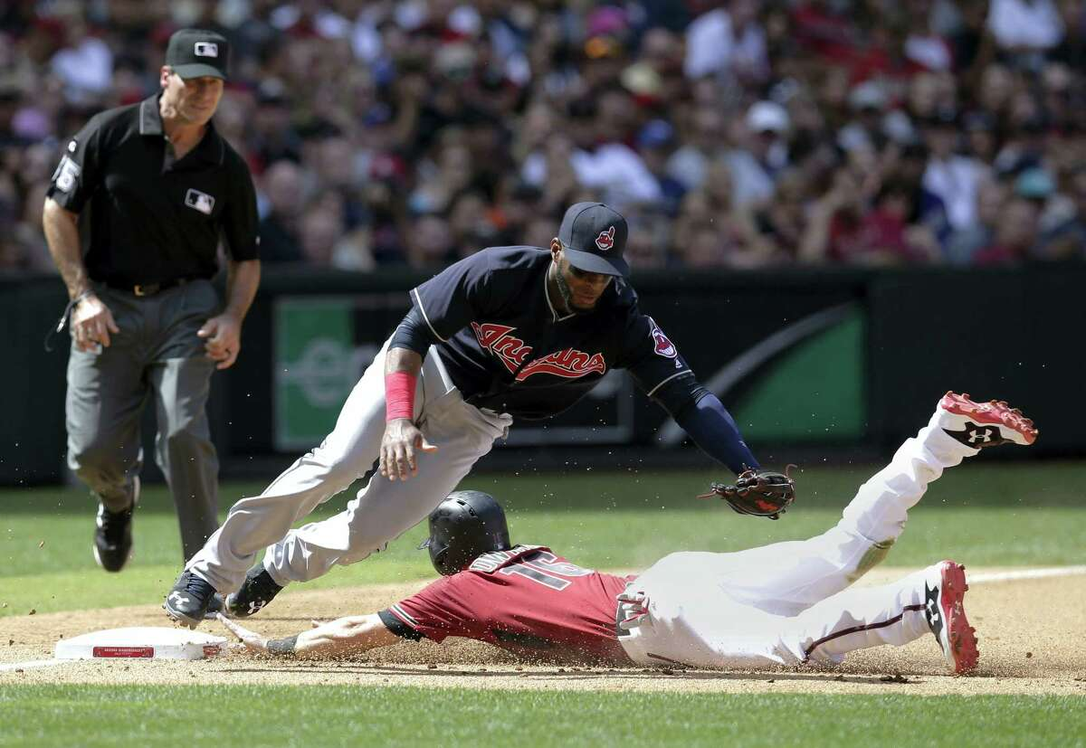 Cleveland Indians third baseman Yandy Diaz, left, tries to put the tag on Arizona Diamondbacks Chris Owings, right, in the fourth inning during a baseball game on April 9, 2017 in Phoenix.