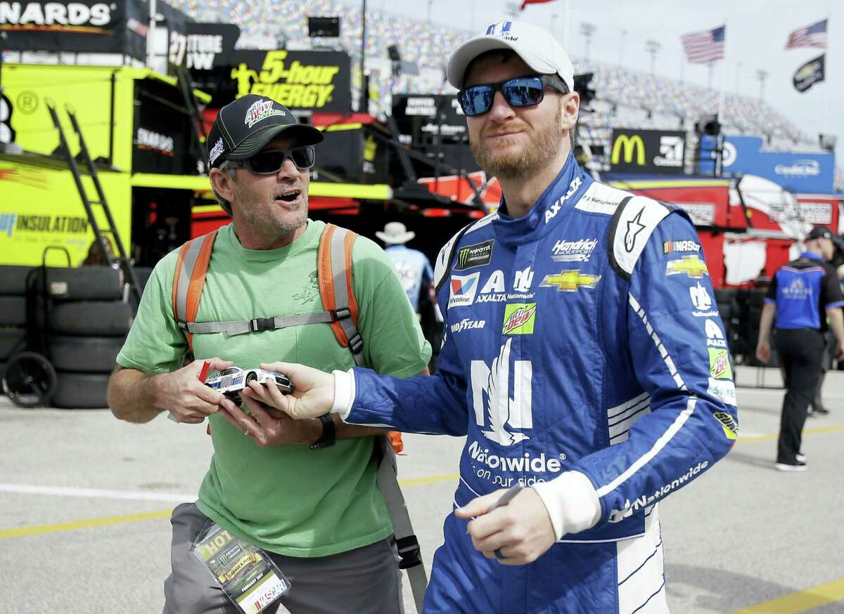 Dale Earnhardt Jr. hands a fan back a model car after he autographed it during a practice session at Daytona International Speedway on Saturday.