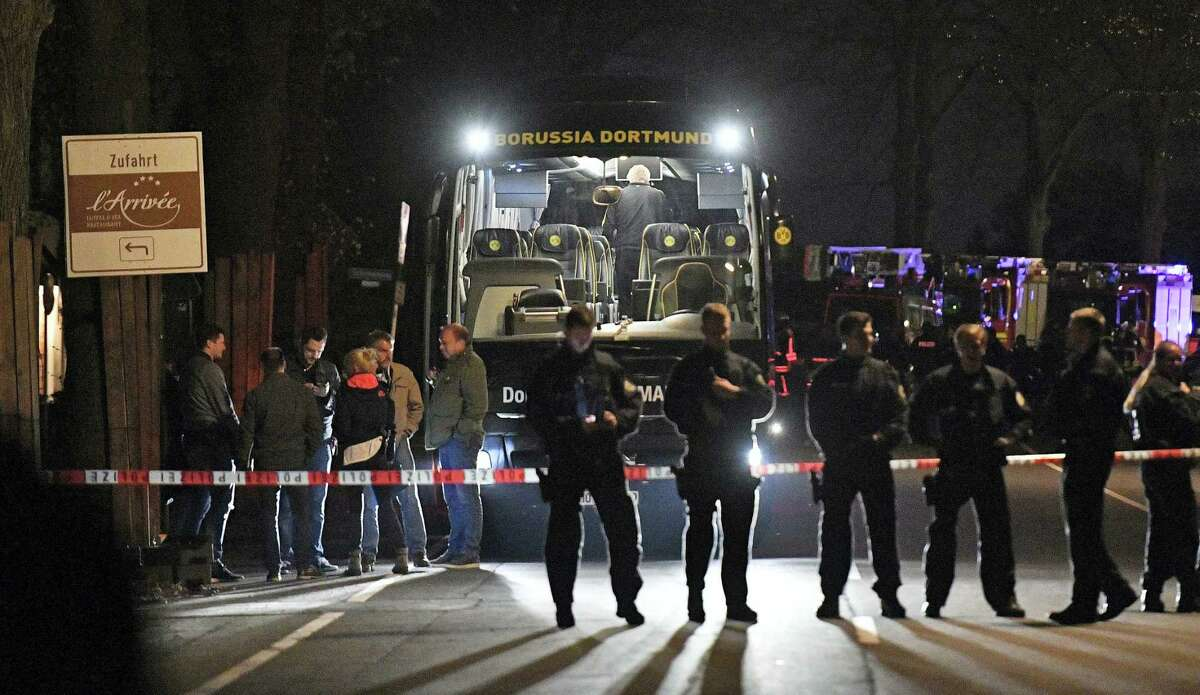 Police officers stand in front of Dortmund's damaged team bus after an explosion before the Champions League quarterfinal soccer match between Borussia Dortmund and AS Monaco in Dortmund, western Germany, Tuesday.