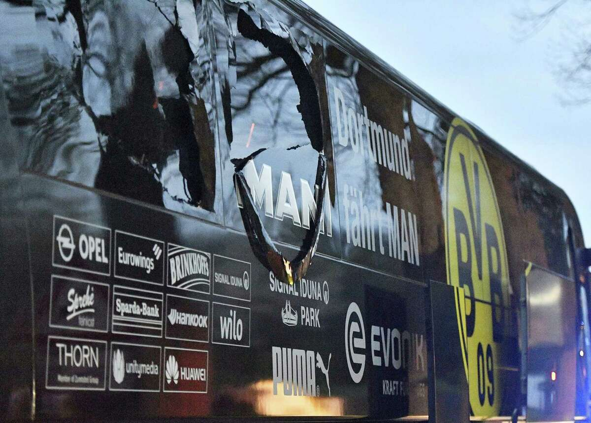 A window of Dortmund's team bus is damaged after an explosion. The team's match against Monaco was rescheduled for Wednesday.