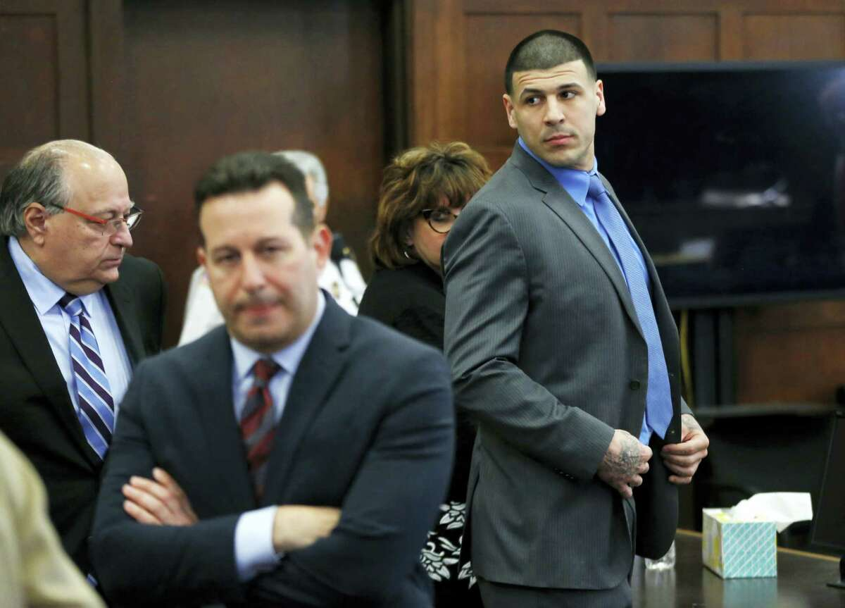 Defendant Aaron Hernandez, right, stands and looks as his attorneys confer during his double murder trial at Suffolk Superior Court, Tuesday, April 11, 2017, in Boston. Hernandez is on trial for the July 2012 killings of Daniel de Abreu and Safiro Furtado who he encountered in a Boston nightclub. The former New England Patriots NFL player is already serving a life sentence in the 2013 killing of semi-professional football player Odin Lloyd.