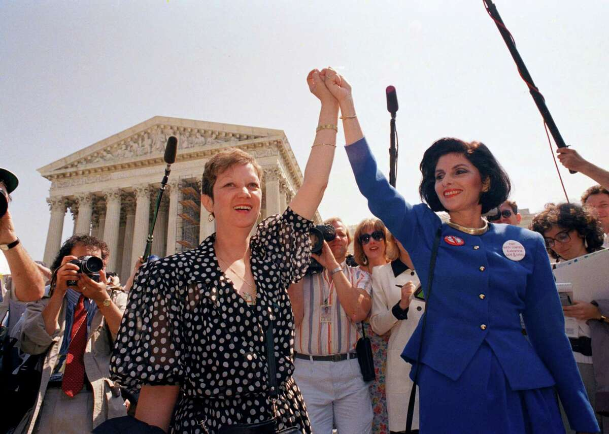 In this April 26, 1989 file photo, Norma McCorvey, Jane Roe in the 1973 court case, left, and her attorney Gloria Allred hold hands as they leave the Supreme Court building in Washington after sitting in while the court listened to arguments in a Missouri abortion case. McCorvey died at an assisted living center in Katy, Texas on Saturday, Feb. 18, 2017, said journalist Joshua Prager, who is working on a book about McCorvey and was with her and her family when she died. He said she died of heart failure.