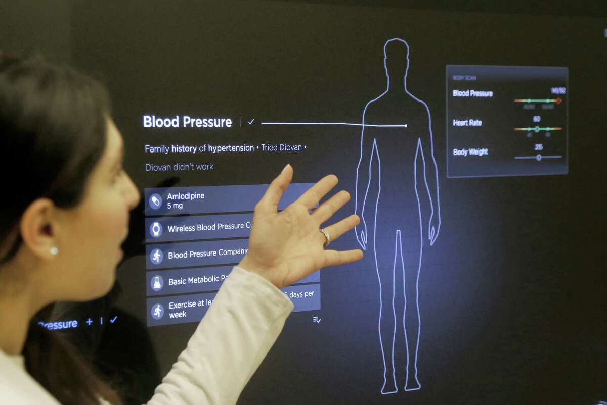 Dr. Aaliya Yaqub points to a large monitor while giving a demonstration of medical checkup at a Forward medical office in San Francisco.