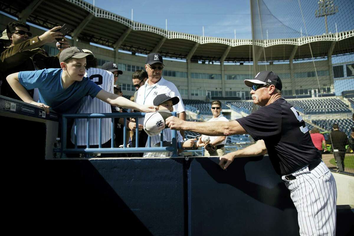 """Yankees guest instructor Rich """"Goose"""" Gossage signs autographs during a spring training workout Friday in Tampa, Fla."""