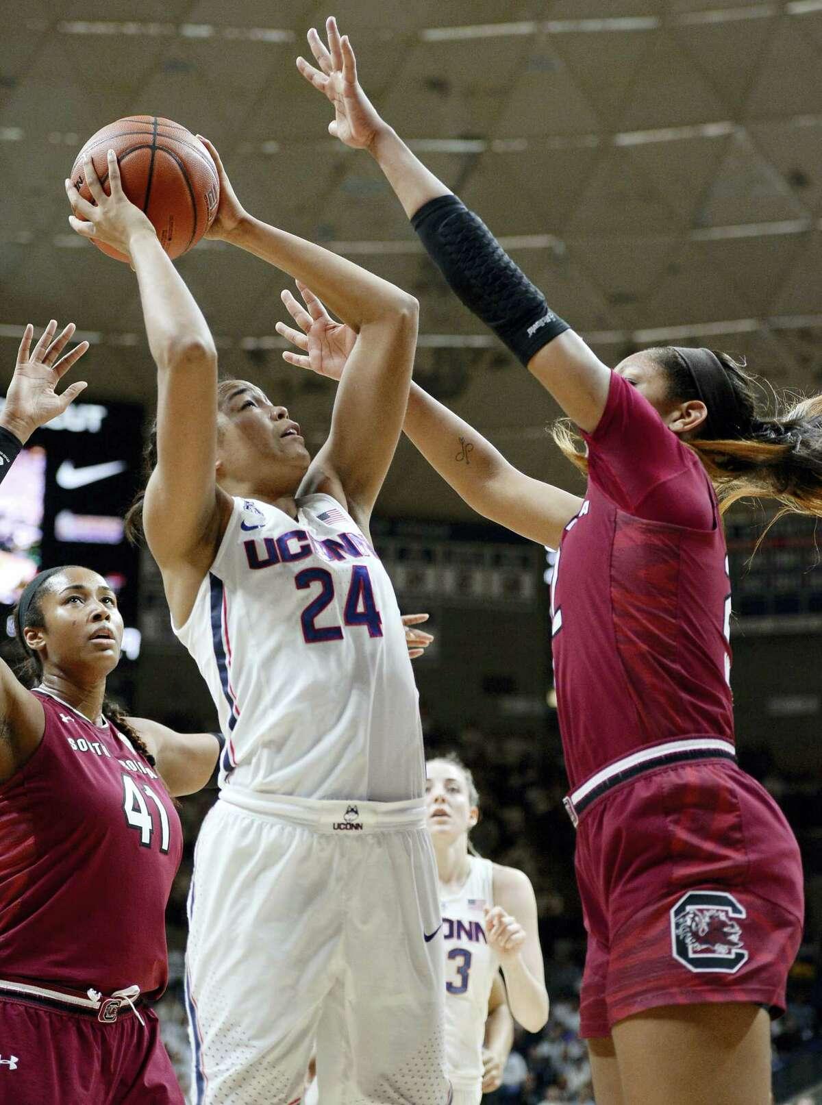 UConn's Napheesa Collier, center, shoots as South Carolina's Alaina Coates, left, and South Carolina's A'ja Wilson, right, defend on Monday.