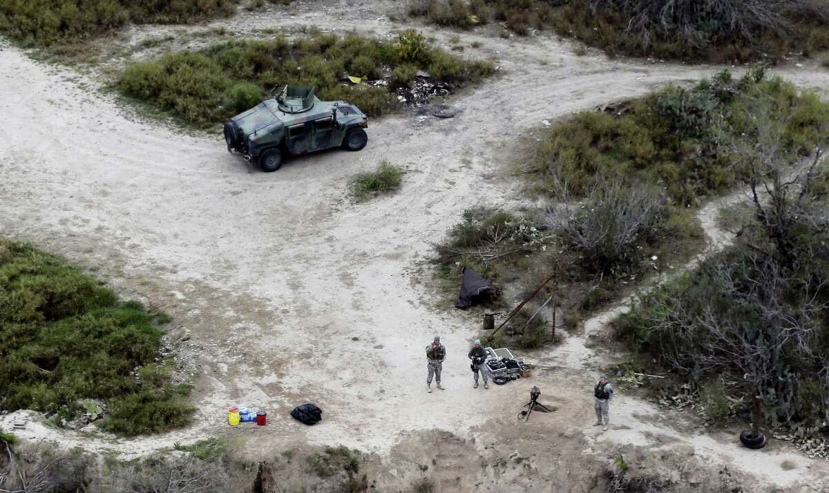 In this file photo, members of the National Guard patrol along the Rio Grande at the Texas-Mexico border in Rio Grande City, Texas. The Trump administration is considering a proposal to mobilize as many as 100,000 National Guard troops to round up unauthorized immigrants, including millions living nowhere near the Mexico border, according to a draft memo obtained by The Associated Press.