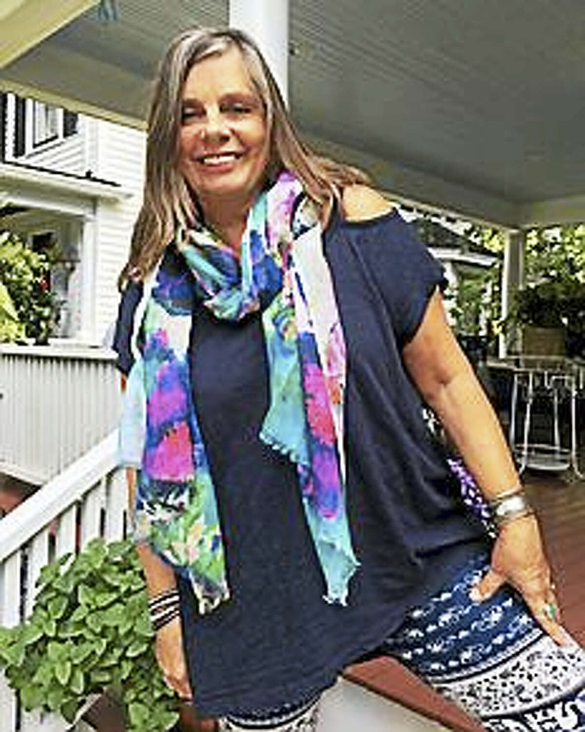 "Boston fashion designer Pam Kubbins wears one of the three scarves she created from the painting ""Wild Roses on Organic Cotton"" by Barkhamsted artist and writer Carol Wallace."