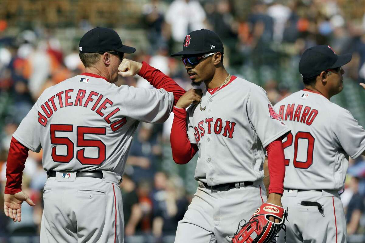 Boston Red Sox third base coach Brian Butterfield greets outfielder Mookie Betts after the team's 7-5 win over the Detroit Tigers in a baseball game, Sunday in Detroit.