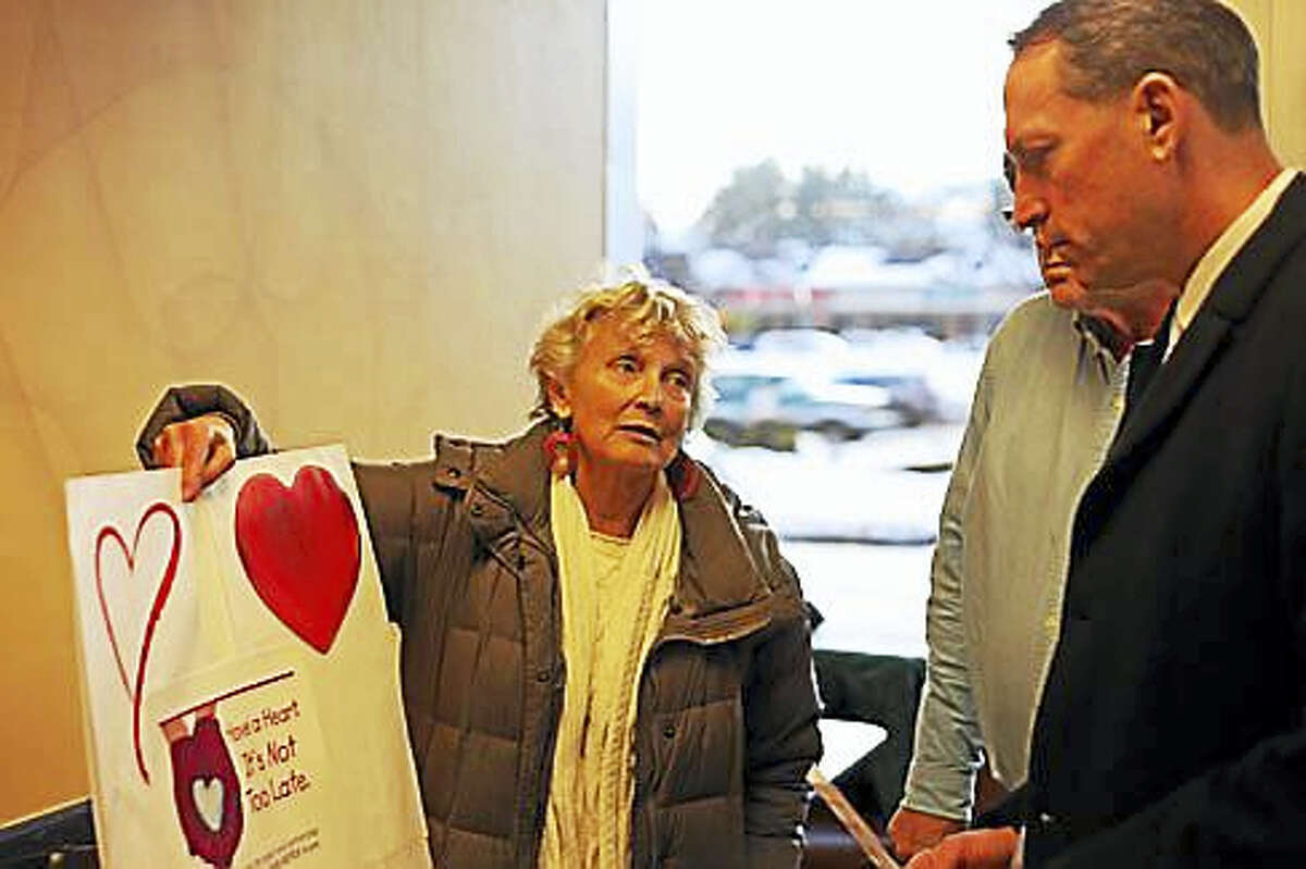 """Jan Carlsson-Bull presents Sen. Paul Doyle with a """"valentine"""" for consideration."""