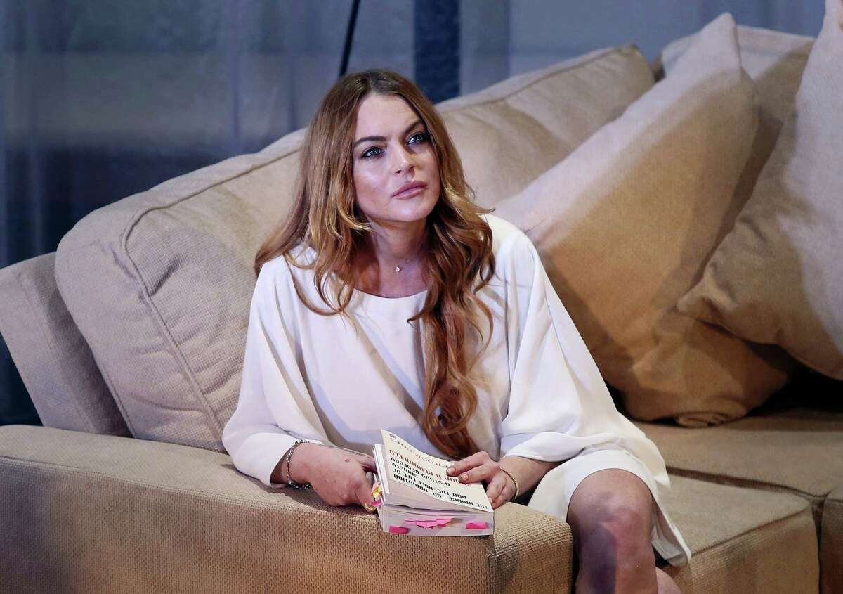 """In this Sept. 30, 2014, file photo, actress Lindsay Lohan performs a scene from the play, """"Speed the Plow,"""" during a photocall at the Playhouse Theatre in central London. Lohan told the Daily Mail on Friday, Feb. 10, 2017, that Americans should come together to support President Donald Trump."""