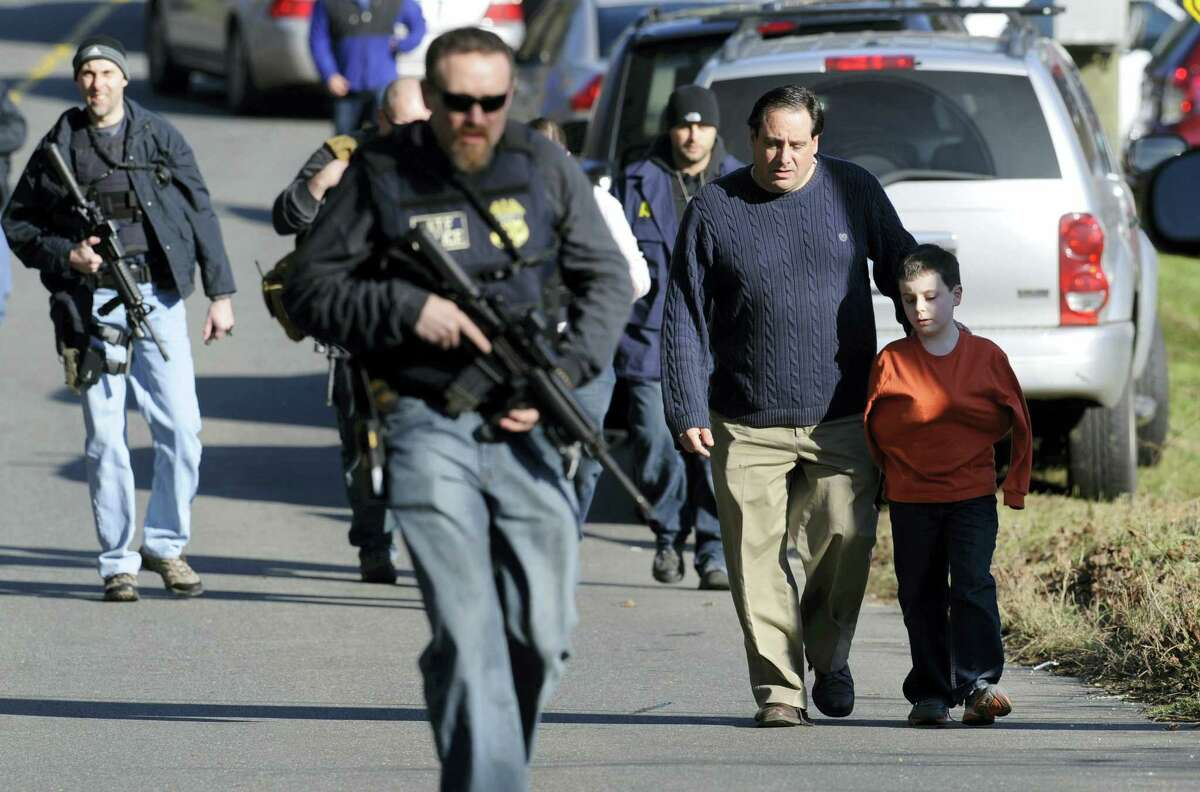 In this Friday, Dec. 14, 2012 photo, parents leave a staging area after being reunited with their children following a shooting at the Sandy Hook Elementary School in Newtown, Conn., where Adam Lanza fatally shot 27 people, including 20 children. The Republican-led Senate voted on Feb. 15, 2017 to block an Obama-era regulation that would prevent an estimated 75,000 people with mental disorders from being able to purchase a firearm.
