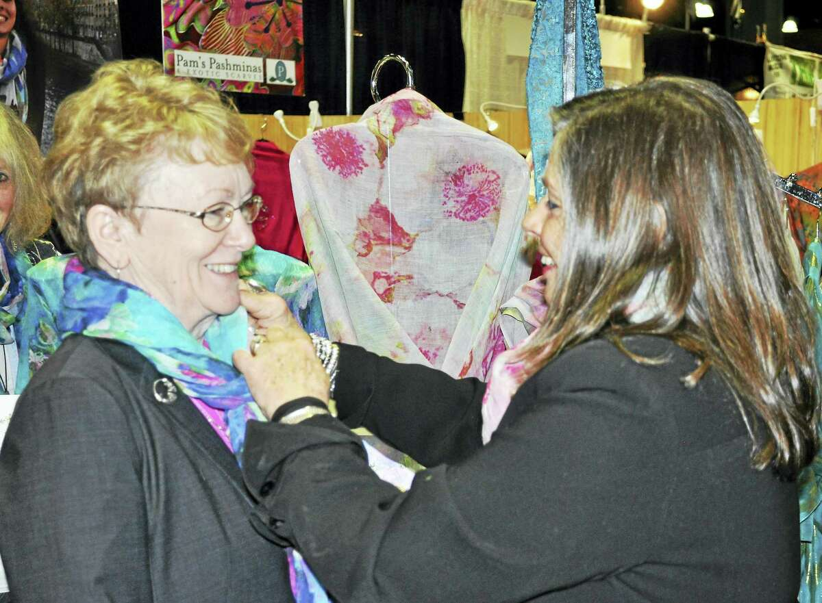 Pam Kubbins fine tunes a scarf worn by Phyllis Wells of Barkhamsted, at the Connecticut Flower Show.
