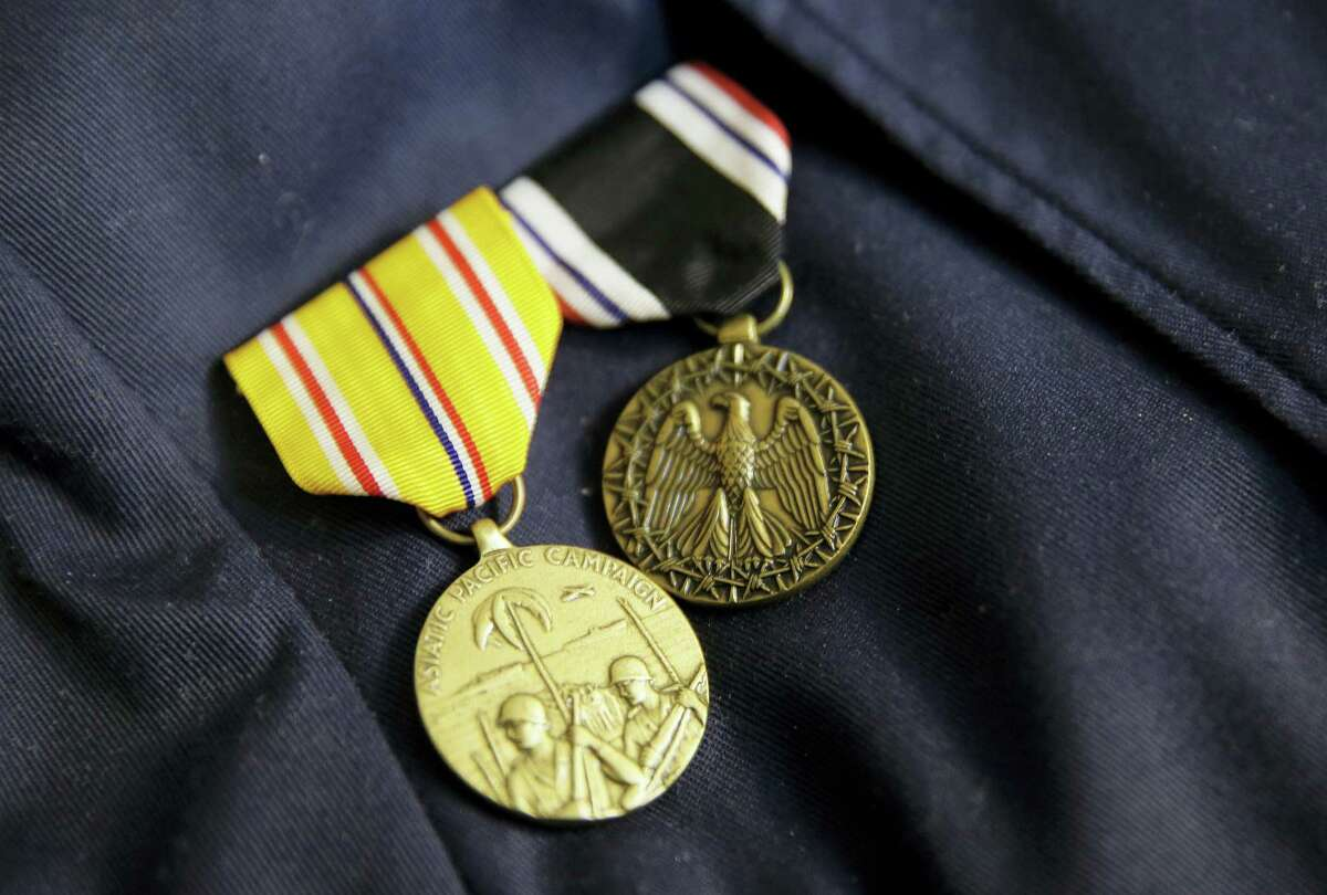 In this photo taken Thursday, April 6, 2017, a pair of medals are pinned to the jacket of Bataan Death March survivor Ramon Regalado at his home in El Cerrito, Calif. Survivors of the infamous Bataan Death March in the Philippines are marking the anniversary Saturday in San Francisco with speeches and a 21-gun battery salute to the thousands who died in it. Among the speakers will be Regalado, a former wartime machine-gun operator who turns 100 this month and is among the war's few living survivors.