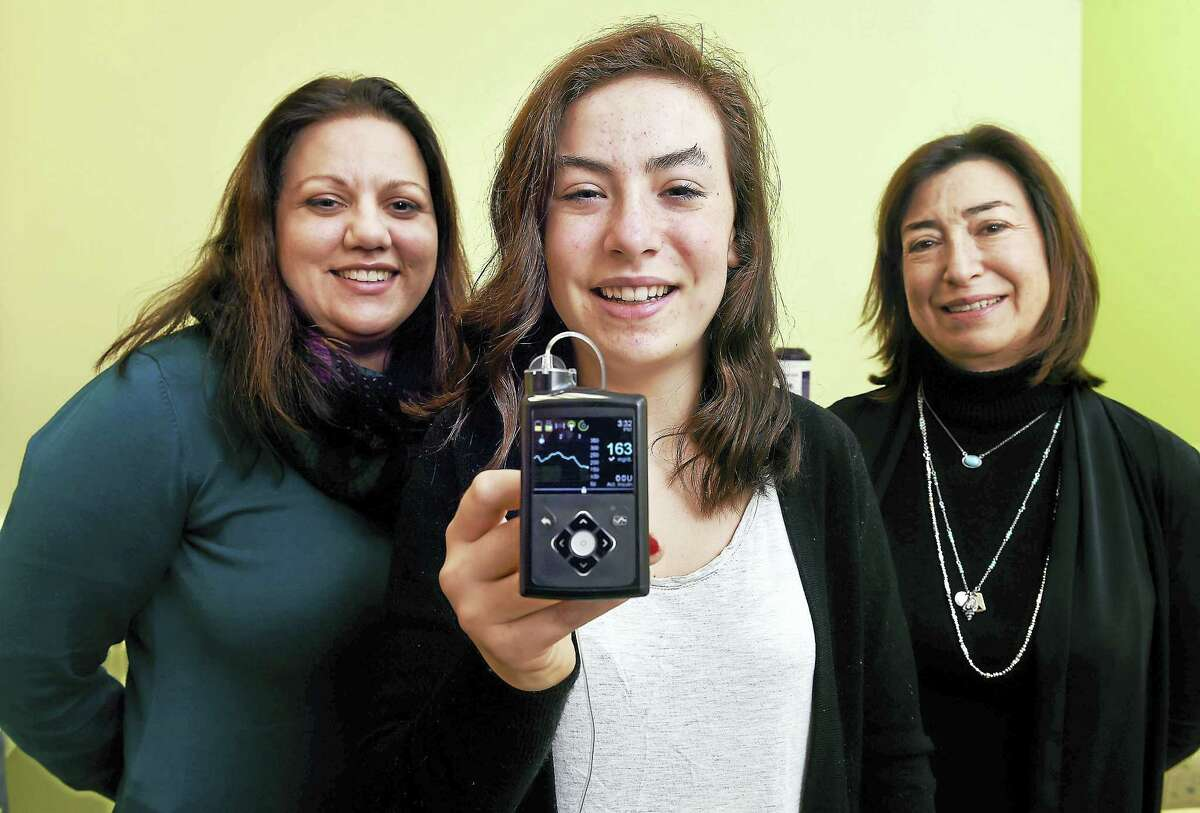 Claire Bickel, center, 14, of Branford holds a monitor that is part of the Medtronic MiniMed670G insulin pump system. With her are her pediatric endocrinologist, Dr. Jennifer Sherr, left, and mother, Francesca Bickel, at the Pediatric Specialty Center in New Haven. The display shows her blood sugar level.